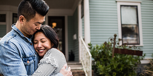 Smiling man in jean jacket tightly hugs wife in striped shirt while standing in front yard outside of their home