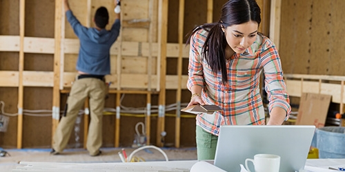 Woman checks laptop while man is working in the background on new home construction project