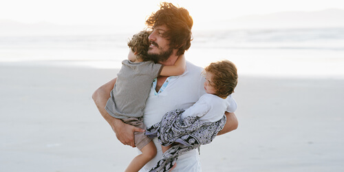A father in a white tee holds his two children as they walk on the beach.