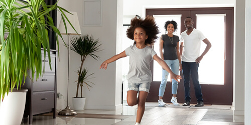 A young girl runs into her new home past some tropical plants as her parents stand smiling by the front door.