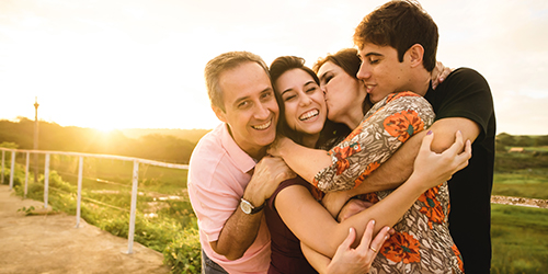 A mother and father hug and kiss their adult son and daughter outdoors at sunset.