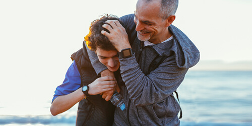 A father wearing a gray hoodie wraps his arm around his son who is wearing a blue shirt and black vest as they walk along a beach