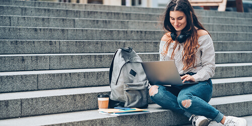 A female college student with long hair, ripped jeans and headphones around her neck, sits with her backpack and coffee on outdoor steps while using her laptop.