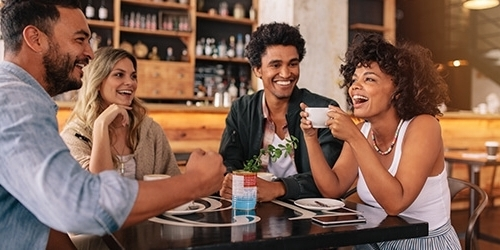 A woman with curly hair holds her cup of coffee while laughing with a group of friends at a cafe.