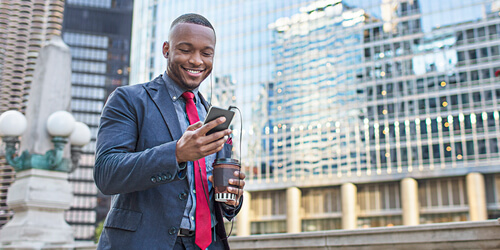 A smiling man in blazer walks in the city wearing headphones and using his mobile phone while holding a coffee.