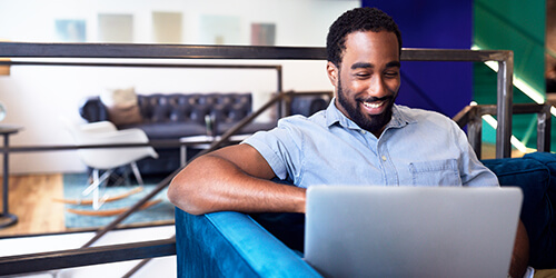 Bearded man sitting on blue couch in denim short sleeve shirt smiles at laptop computer on his lap
