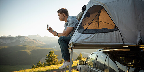 Man camping with a view of the mountains looking at his mobile phone while sitting outside his roof top tent