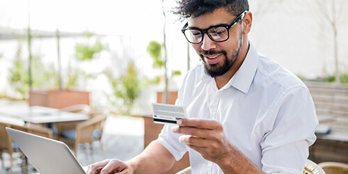 Man in white shirt enters credit card details on his laptop to complete an online purchase