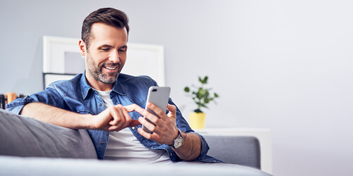 Smiling, casually dressed man sitting on couch texting on mobile phone