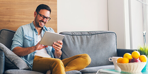 Laughing man wearing glasses and bright gold pants sits on gray couch using his tablet
