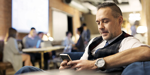 A man wearing a vest and watch uses his mobile phone in a shared office space.