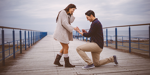 A man on one knee proposes to a woman while they are on a beach boardwalk.