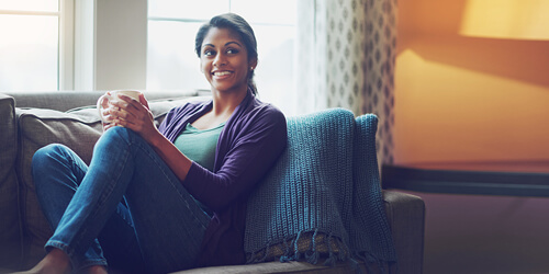 A woman with a ponytail and purple sweater sits on a couch with a blue blanket while holding a drink mug.