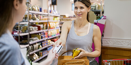 Woman in gray tank top handing her credit card to a grocery clerk for a purchase