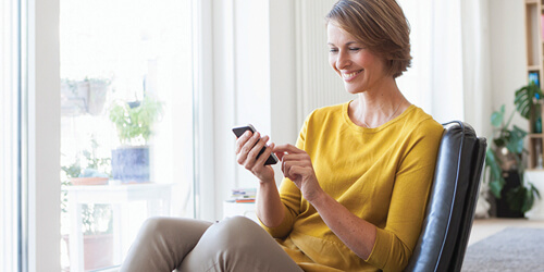 A woman in yellow sits in a chair by a large bright window smiling as she uses her mobile phone.
