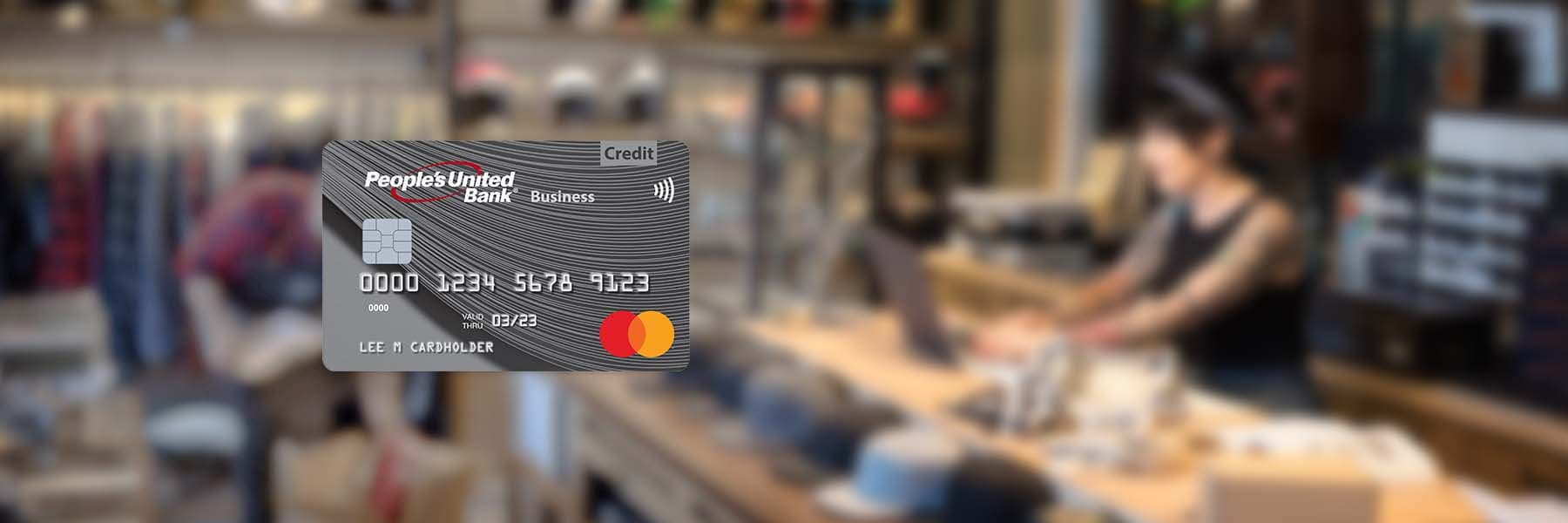 People's United Bank MasterCard business credit card on top of a blurred image of workers in a retail biker accessories, helmets and hats shop.