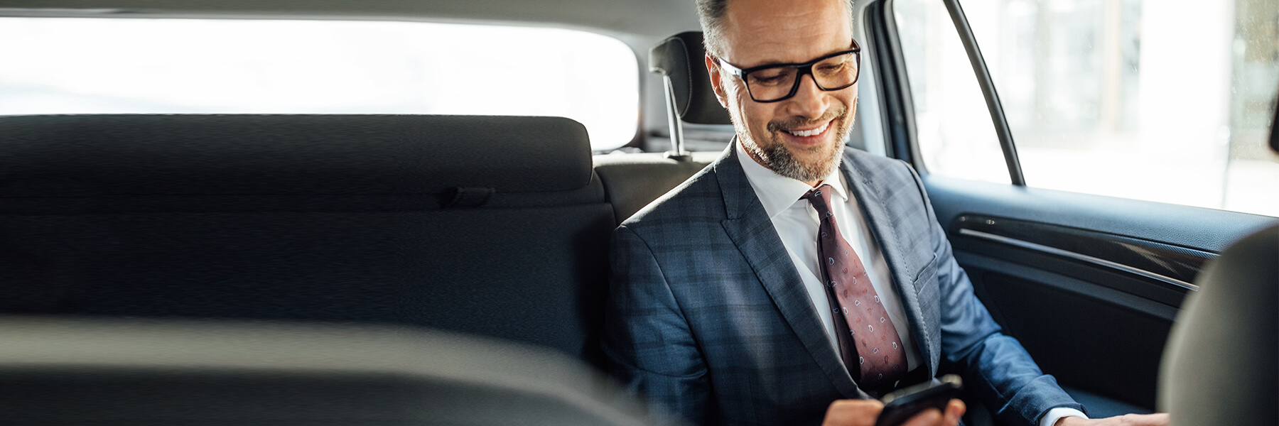 Affluent business man with beard and glasses wearing expensive suit sits in back of town car smiles at mobile phone in hand