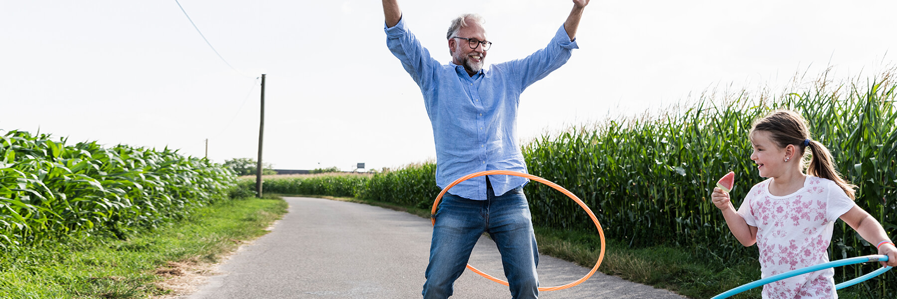 Father with gray beard and glasses raises his hands and young daughter eating a popsicle try to hula hoop on a paved pathway