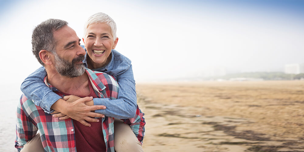 Mature husband in plaid shirt looks back at his wife with short gray hair on his back laughing as they walk on the beach
