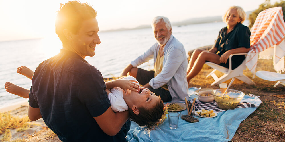 During a sunset picnic on the beach a father holds his son in lap laughing as the grandparents smile and watch