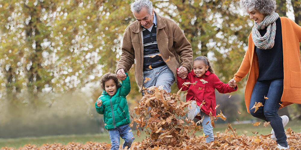 Grandfather and grandmother hold hands with grandson and granddaughter and skip through the leaves on a cool Fall day