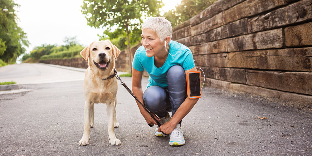 Mature woman with headphones in jogging outfit stops to kneel next to her yellow Labrador retriever on leash to pose for photo