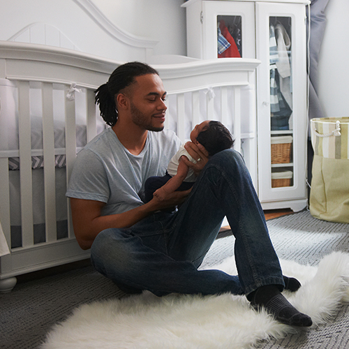 Happy father sits on floor of nursery with white crib and dresser while watching and cradling infant on one raised knee