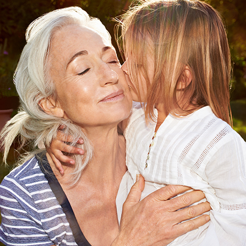 Young blond girl kisses her youthful looking grandmother with eyes closed on the check as she holds her outside in the yard
