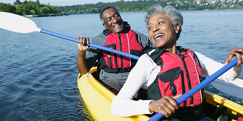 Mature couple in red personal flotation devices enjoy their retirement in a yellow tandem kayak on a quiet lake