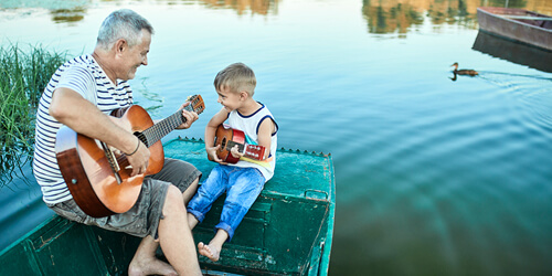 A grandfather and grandson sit on a rowboat in a lake and play their guitars.