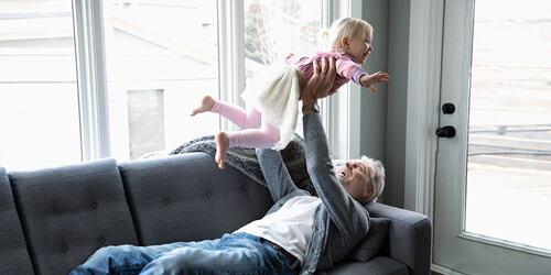 A grandfather laying on a couch lifts his granddaughter into the air by bright sunny windows.