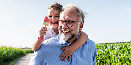 Father with beard and glasses on paved path carries daughter on his back while she enjoys a pink Popsicle on a sunny day