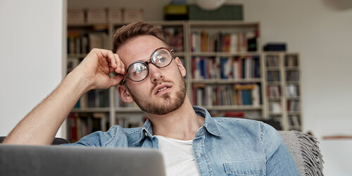A man in glasses sits with his laptop in front of a bookshelf and rests his head in his hand in thought.