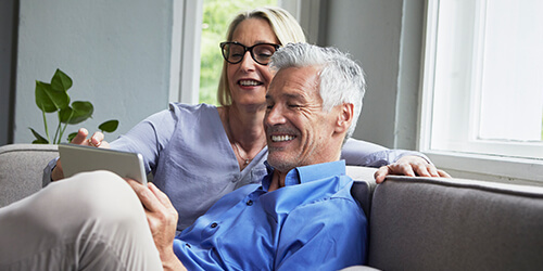 Mature husband in blue shirt holds tablet with wife in glasses pointing to screen relax and bank online on the couch at home
