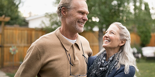 Mature man smiles at wife who is looking up at him as they enjoy time together in the backyard of their home