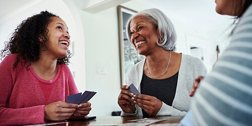 Affluent Grandmother enjoys conversation and a card game with her teenage granddaughter at home